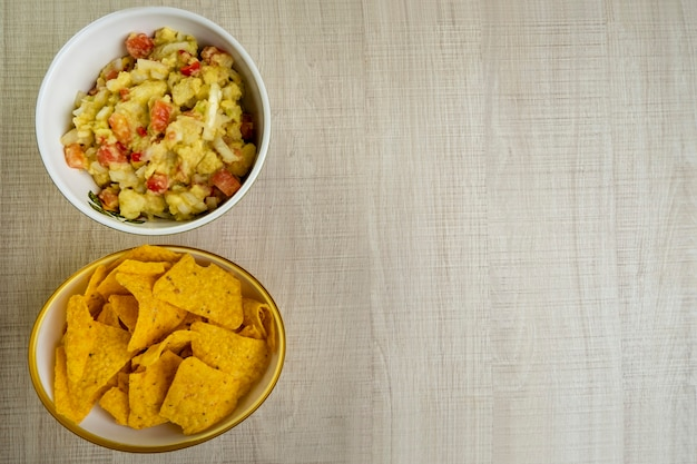 Guacamole com tortilhas na mesa de madeira.