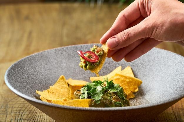 Guacamole de abacate mexicano com nacho, pimenta e manjericão em um prato cinza. mão molha nacho em guacamole