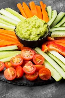 Guacamole de molho latino-americano tradicional em uma tigela e vários legumes (cenoura, tomate, pepino, aipo) sobre um fundo escuro.
