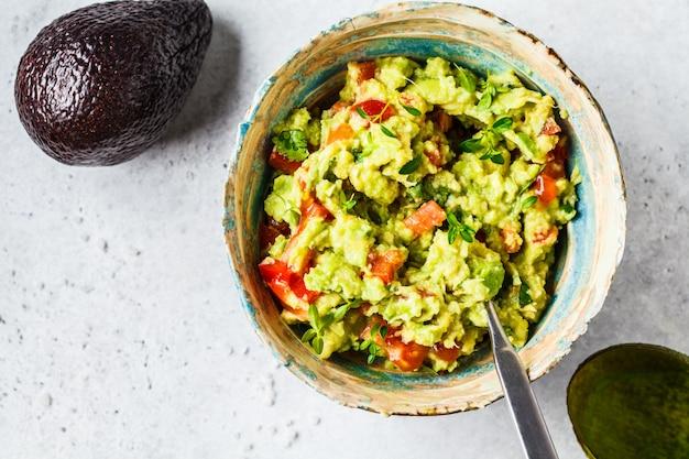 Guacamole fresco do tomate do abacate em uma bacia conceito saudável do alimento baseado da planta