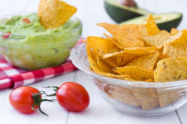 Guacamole mexicano com nachos na mesa de madeira branca
