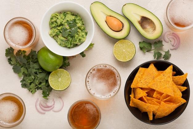 Guacamole, salgadinhos de milho e cerveja, lanche mexicano leve ou jantar, vista superior