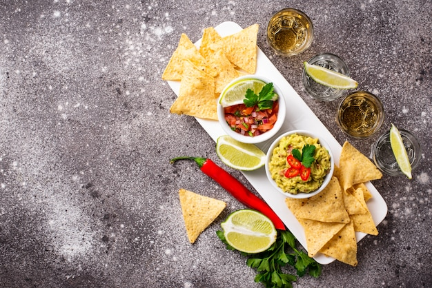 Guacamole, salsa, nachos de batatas fritas e tequila
