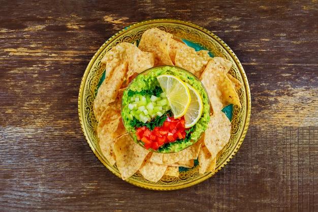 Guacamole verde com nachos e abacate no fundo de madeira