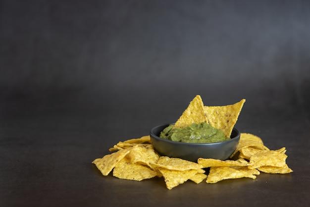 Guacamole verde com nachos na tigela no escuro