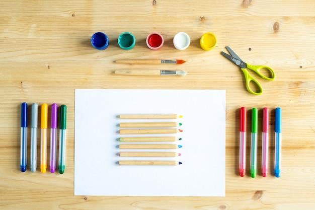 Guaches coloridos, pincéis, tesouras, lápis de cor em uma folha de papel em branco e marcadores de texto sobre a mesa de madeira