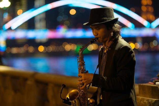 Guangzhou, china - 15 de março de 2016: homem tocando saxofone na rua à noite