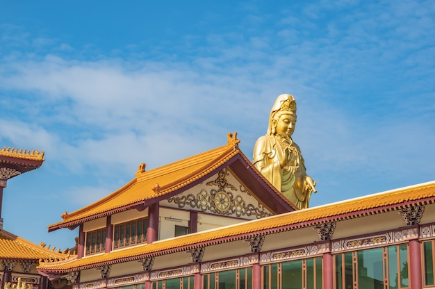 Guanyin madrinha com o telhado do templo e lindo céu no templo foguangshan thaihua, tailândia. para guang shan é uma das quatro grandes organizações budistas em taiwan