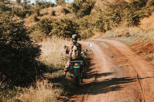 Guarda anti-caça furtiva em uma motocicleta, em uma estrada de terra