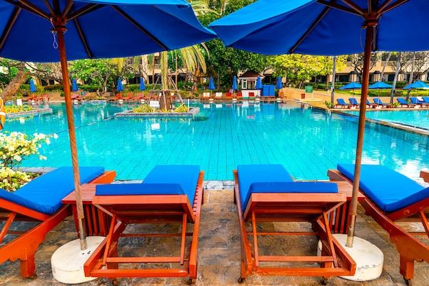 Guarda-chuva bonito e cadeira ao redor da piscina no hotel e resort. férias e concerto de feriado