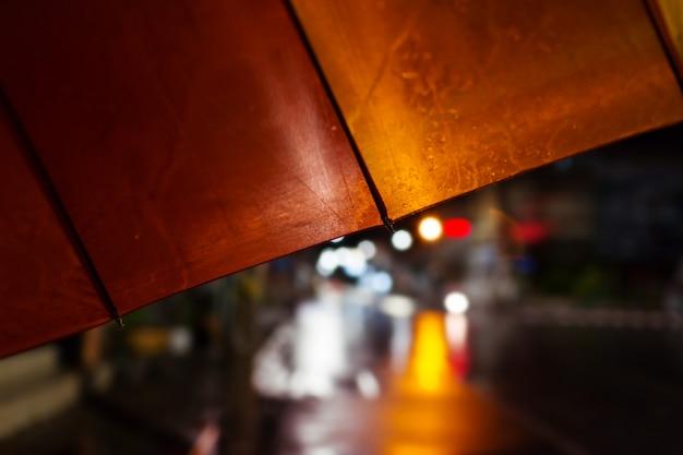 Guarda-chuva, chuva forte cair à noite, foco seletivo e cor em tons.