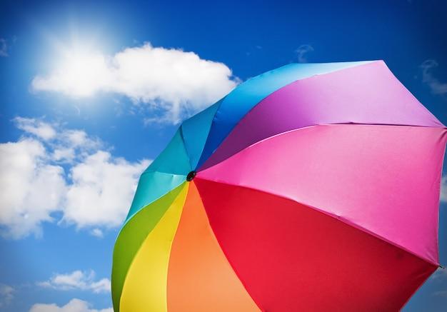 Guarda-chuva colorida contra o céu com o sol