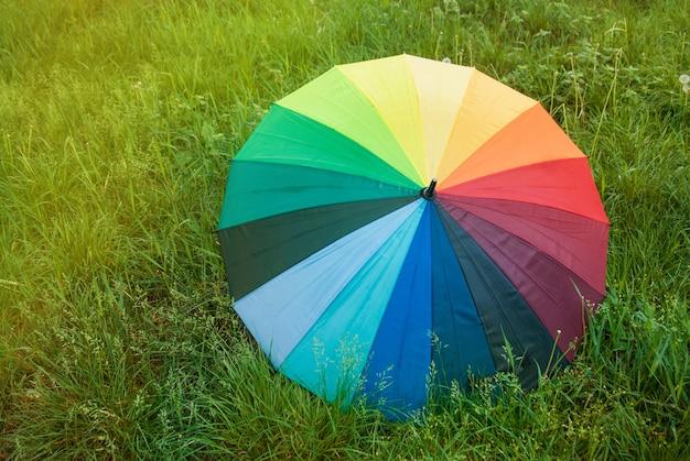 Guarda-chuva colorido do arco-íris na grama verde. tempo de primavera.