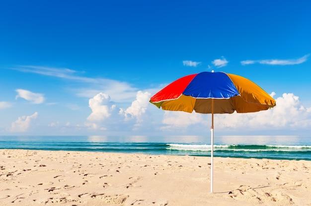 Guarda-chuva colorido e linda praia de areia