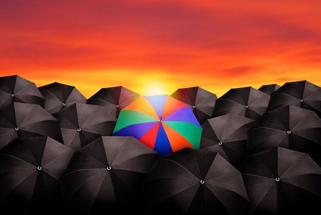 Guarda-chuva colorido na massa de guarda-chuvas pretos.
