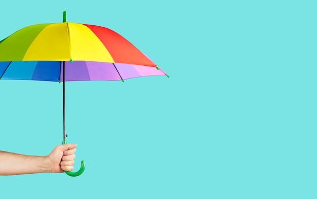 Guarda-chuva cor de arco-íris na mão masculina sobre fundo verde