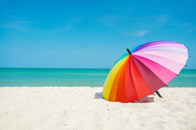Guarda-chuva de arco-íris na areia da praia