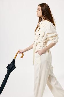 Guarda-chuva de macacão branco de mulher bonita nas mãos fechadas os olhos moda luz de fundo. foto de alta qualidade