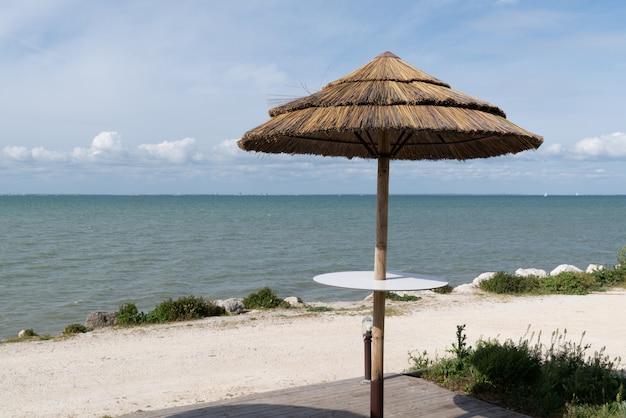 Guarda-chuva de palha na praia em um dia ensolarado
