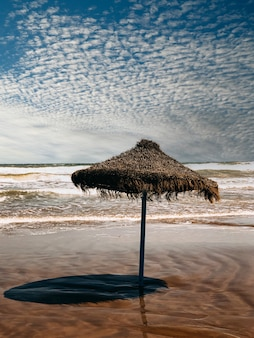 Guarda-chuva de palha solitário na praia