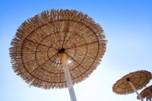 Guarda-chuva de teto solar de cabana na grama seca com reflexo de lente