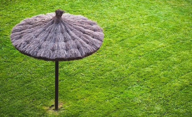 Guarda-chuva de urze no chão de grama verde para deitar e relaxar em um dia ensolarado de verão.