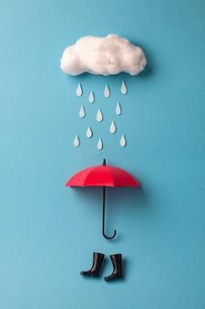 Guarda-chuva e botas de chuva sob a nuvem no céu azul