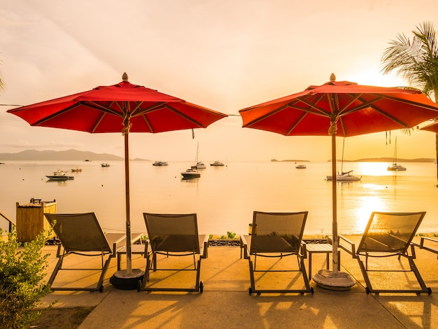 Guarda-chuva e cadeira ao redor da piscina ao ar livre no hotel e resort