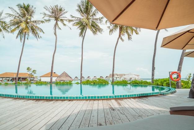 Guarda-chuva e cadeira ao redor da piscina em hotel resort