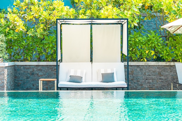Guarda-chuva e cadeira ao redor da piscina externa em hotel resort para viagens de lazer conceito de férias