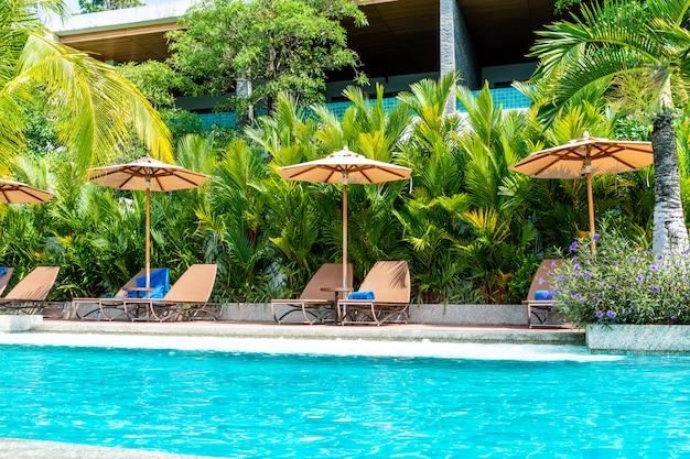 Guarda-chuva e cadeira ao redor da piscina no hotel e resort