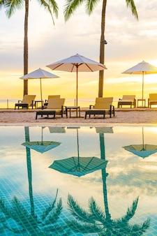 Guarda-chuva e cadeira ao redor da piscina no hotel resort com o nascer do sol da manhã. conceito de férias e férias
