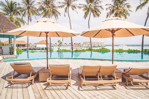 Guarda-chuva e cadeira ao redor da piscina no hotel resort