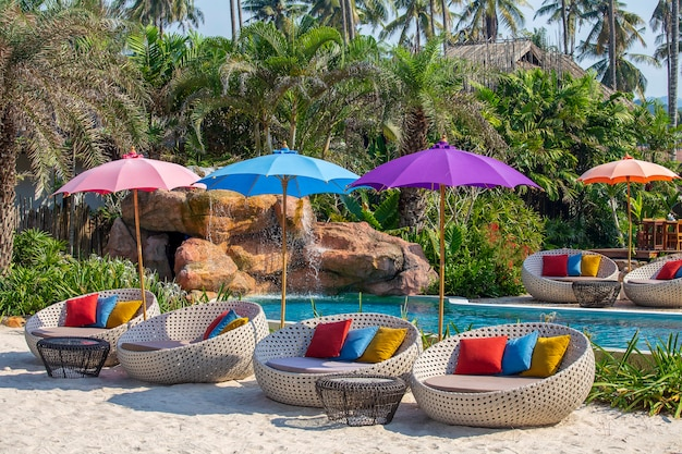 Guarda-chuva e cadeira ao redor da piscina no resort tropical. conceito de férias e férias
