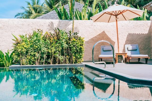 Guarda-chuva e cadeira ao redor da piscina perto da praia do mar oceano com céu azul e nuvem branca
