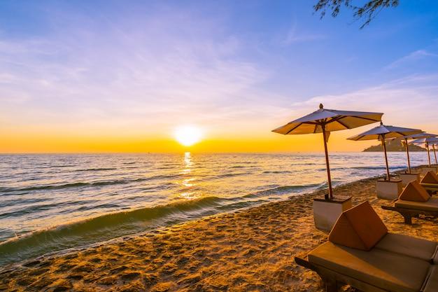 Guarda-chuva e cadeira com travesseiro em torno da bela paisagem da praia e do mar