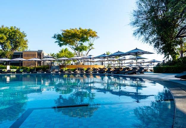 Guarda-chuva e cadeira de luxo bonito em torno da piscina no hotel e resort com céu azul