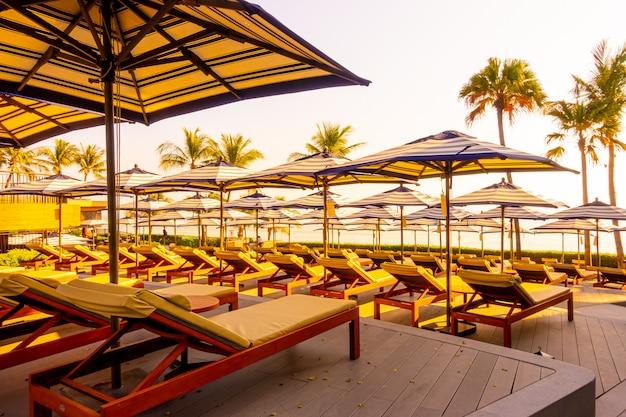 Guarda-chuva e cadeira de luxo bonito em torno da piscina no hotel e resort