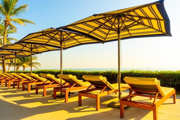 Guarda-chuva e cadeira de luxo bonito em volta da piscina no hotel e resort com palmeira de coco