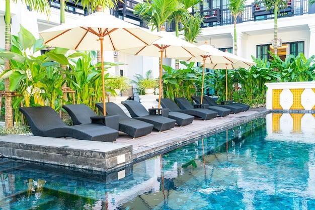 Guarda-chuva e cadeira de piscina ao redor da piscina - conceito de férias e viagens