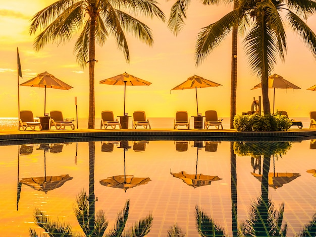 Guarda-chuva e cadeira em torno da piscina exterior de luxo