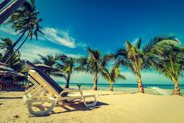 Guarda-chuva e cadeira em torno da praia e do mar para viagens e férias