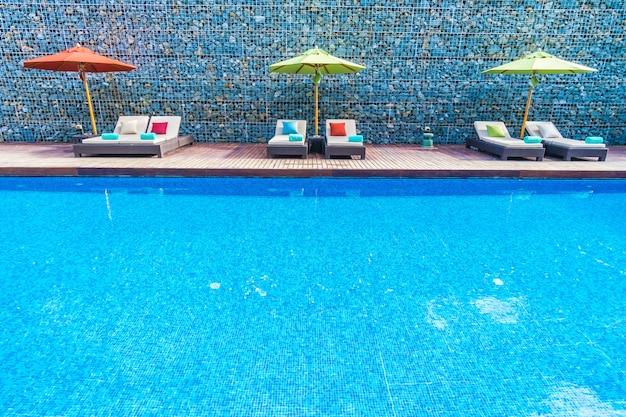 Guarda-chuva e cadeira em volta da piscina