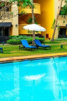 Guarda-chuva e cadeira na piscina com árvores