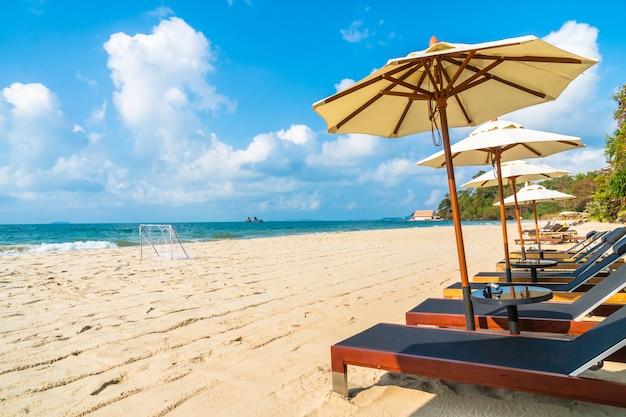 Guarda-chuva e cadeira na praia e no mar