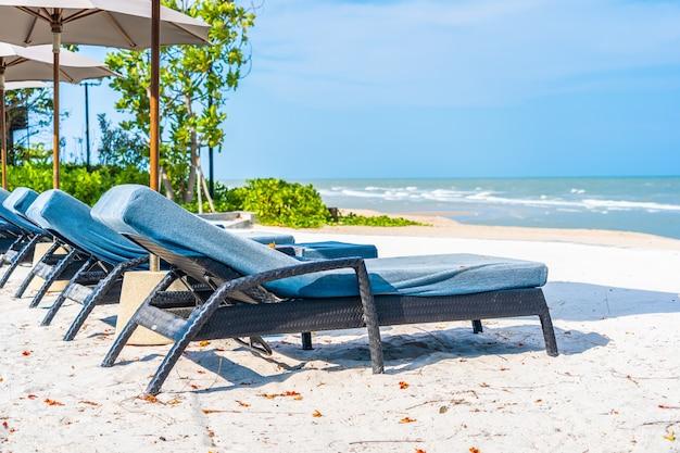 Guarda-chuva e cadeira na praia mar oceano com céu azul e nuvem branca