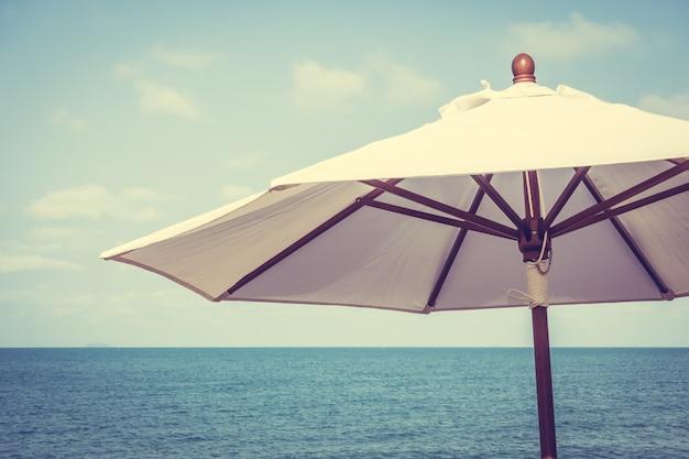 Guarda-chuva e cadeira na praia tropical