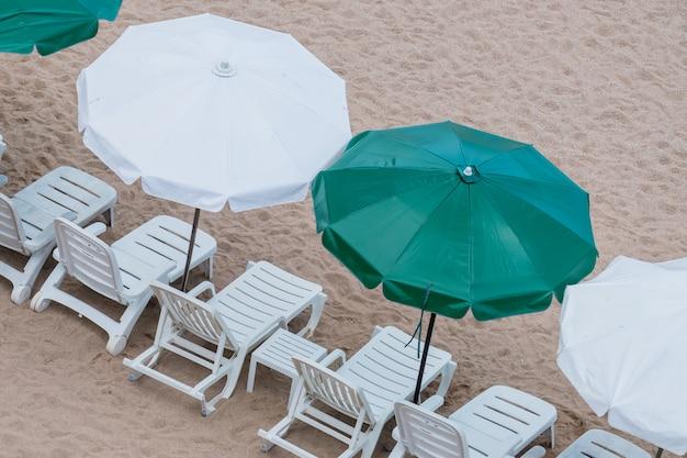 Guarda-chuva e cadeira numa praia tropical, praia de verão na ilha, vista superior