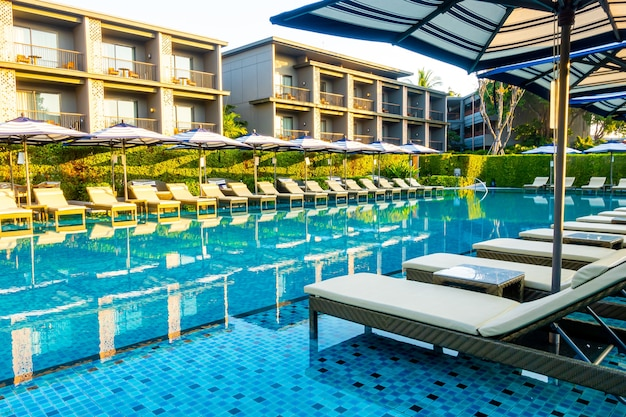 Guarda-chuva e cama ao redor da piscina externa em hotel resort para viagens, férias, férias, conceito