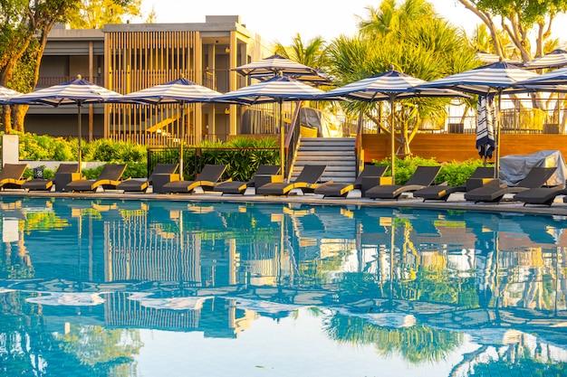 Guarda-chuva e cama de piscina em volta da piscina no hotel resort para viagens de férias
